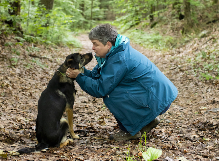 Asha, a border collie mix, leans in as Marilyn Webster kneels to praise her during their walk.